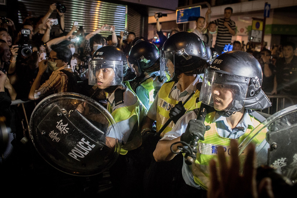 . HONG KONG - OCTOBER 18:  Pro-democracy protesters push police back as they break down barricades and take back streets in Mong Kok on October 18, 2014 in Hong Kong, Hong Kong. Police have begun to take measures to remove the blockades put in place by pro democracy supporters following weeks of protests. Hong Kong\'s Chief Executive Leung Chun-ying today called for talks to resume between protest groups and government officials and said his government is ready to meet with student leaders to discuss \'universal suffrage\'  (Photo by Chris McGrath/Getty Images) *** BESTPIX ***