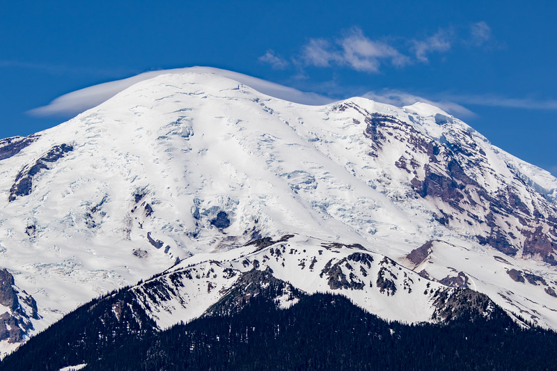 Close-up of Mount Rainier's summit and some smooth clouds slightly wisping over the top