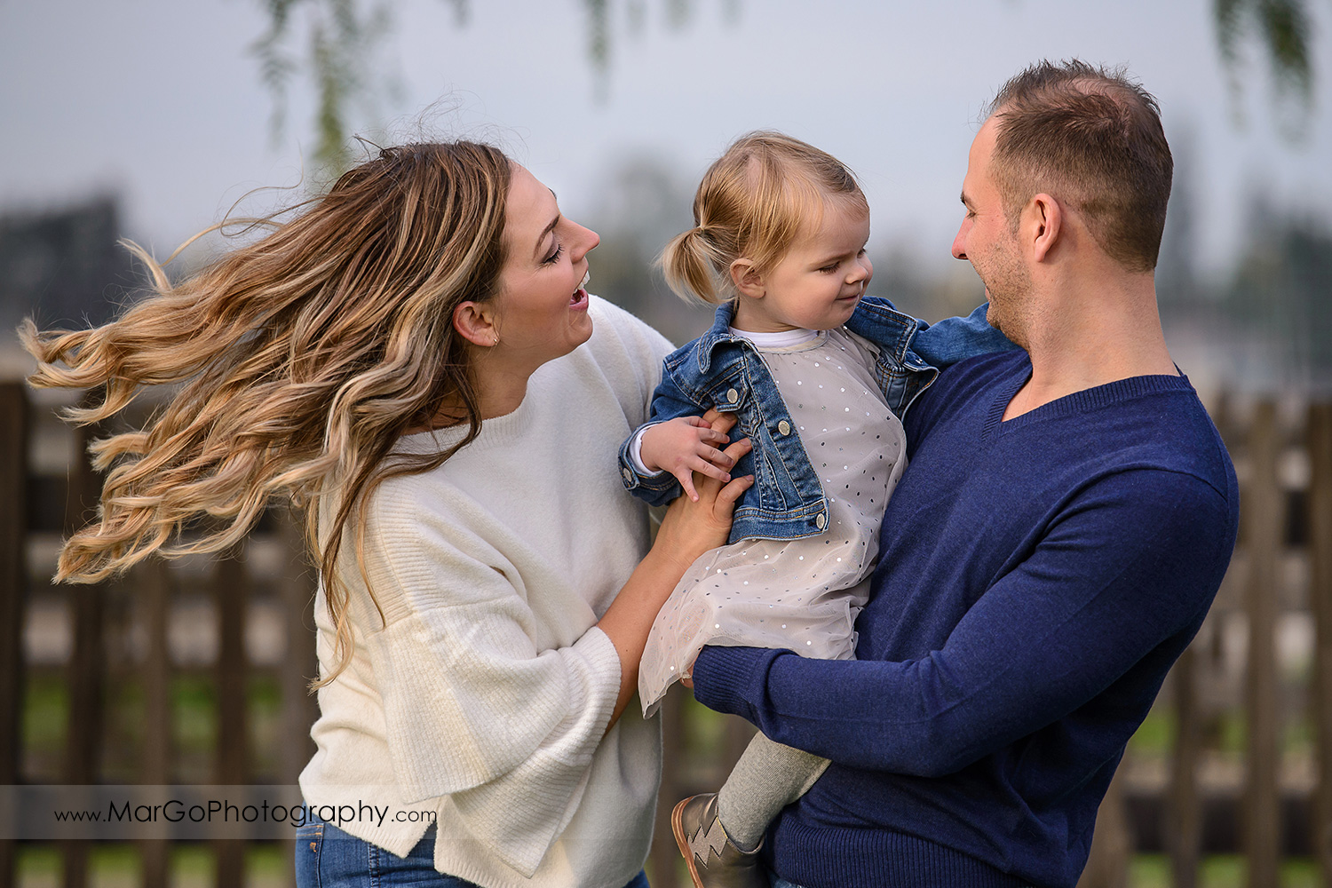close-up portrait of family of three wearing white and navy blue clothes during session at San Jose Martial Cottle Park