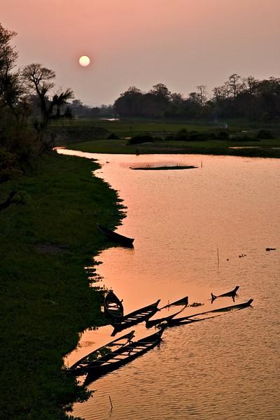 Sunken boats at sunset in a river in Kaziranga national park