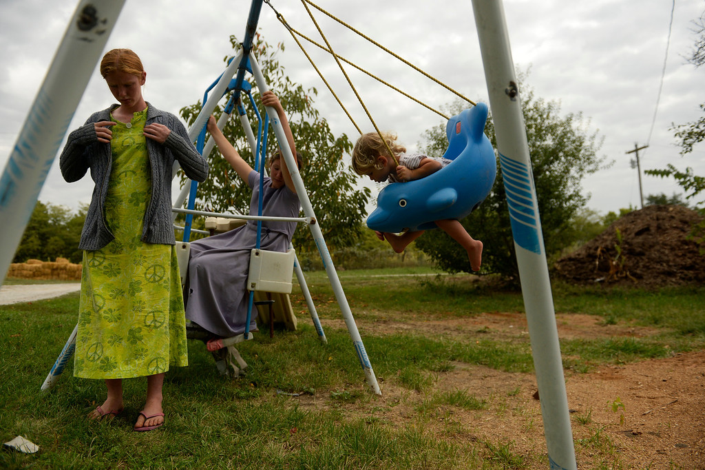 . From left, Sarai Newman, 14, Selah, 10, and Sarahanne, 1, take a moment between chores to relax  at their family farm in Trenton, Mo., Tuesday, September 24, 2013. The older girls help care for Sarahanne when their mother is busy. (Photo By RJ Sangosti/The Denver Post)