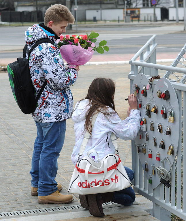 . A couple write their names next to padlocks symbolizing enduring love on the Lovers Bridge in the Wilanow district in Warsaw, Poland, Friday, Feb. 14, 2014. Valentine\'s Day was introduced to Poland after the country shed communism and improved the days sales of heart-shaped sweets, cakes and balloons. (AP Photo/Alik Keplicz)