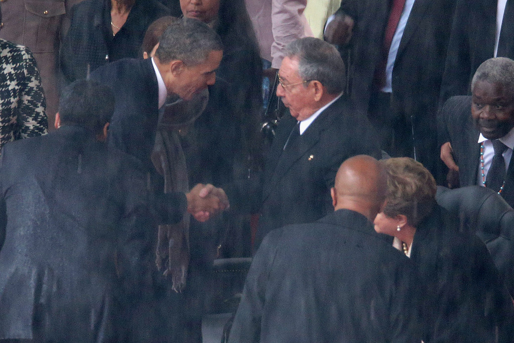 . JOHANNESBURG, SOUTH AFRICA - DECEMBER 10:  U.S. President Barack Obama (L) shakes hands with Cuban President Raul Castro during the official memorial service for former South African President Nelson Mandela at FNB Stadium December 10, 2013 in Johannesburg, South Africa. Over 60 heads of state have travelled to South Africa to attend a week of events commemorating the life of former South African President Nelson Mandela. Mr Mandela passed away on the evening of December 5, 2013 at his home in Houghton at the age of 95. Mandela became South Africa\'s first black president in 1994 after spending 27 years in jail for his activism against apartheid in a racially-divided South Africa.  (Photo by Chip Somodevilla/Getty Images)