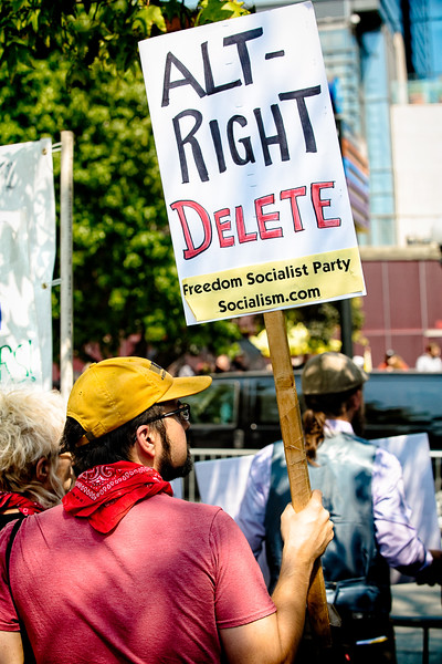 """A counterprotester holds up his, """"ALT-RIGHT DELETE - Freedom Socialist Party Socialism.com,"""" sign."""