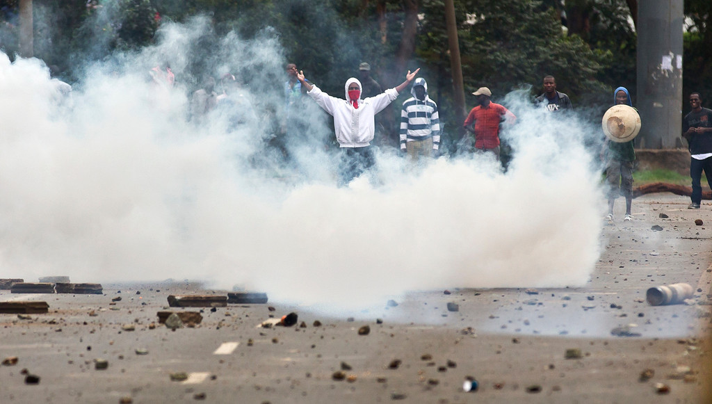 . Students throwing rocks taunt riot police firing tear gas as they engage in running battles on the highway next to Nairobi University\'s main campus in downtown Nairobi, Kenya Tuesday, May 20, 2014. Kenyan university students on Tuesday carried out demonstrations over a proposed increase in student fees, but the protests quickly turned into hours of running battles between students throwing rocks and security forces firing tear gas, before riot police chased the students inside their campus and cornered them in a building into which they fired dozens of tear gas grenades and for a while prevented anyone from leaving. (AP Photo/Ben Curtis)