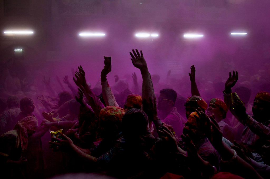. Hindu devotees throw colored powder on each other and dance inside Banke Bihari temple during Holi festival celebrations in Vrindavan, India, Wednesday, March 8, 2017. Holi, the festival of colors celebrates the arrival of spring among other things. (AP Photo/Manish Swarup)