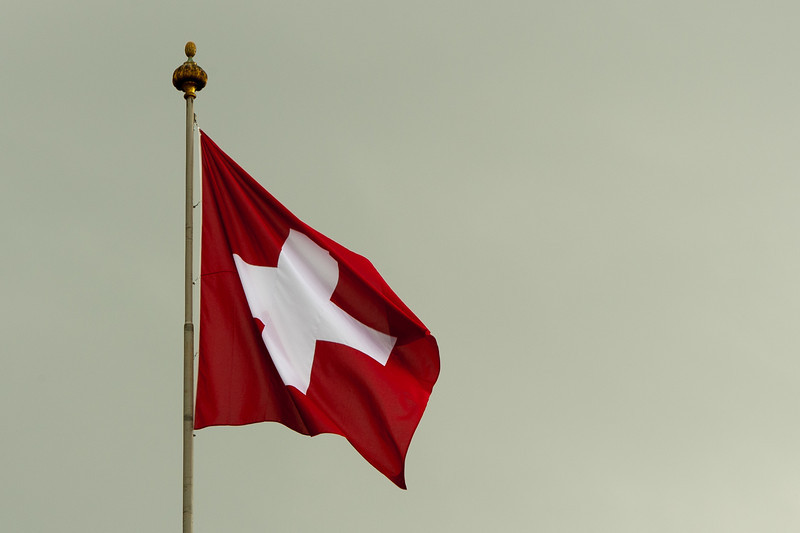 Swiss flag waving from pole in Bern, Switzerland
