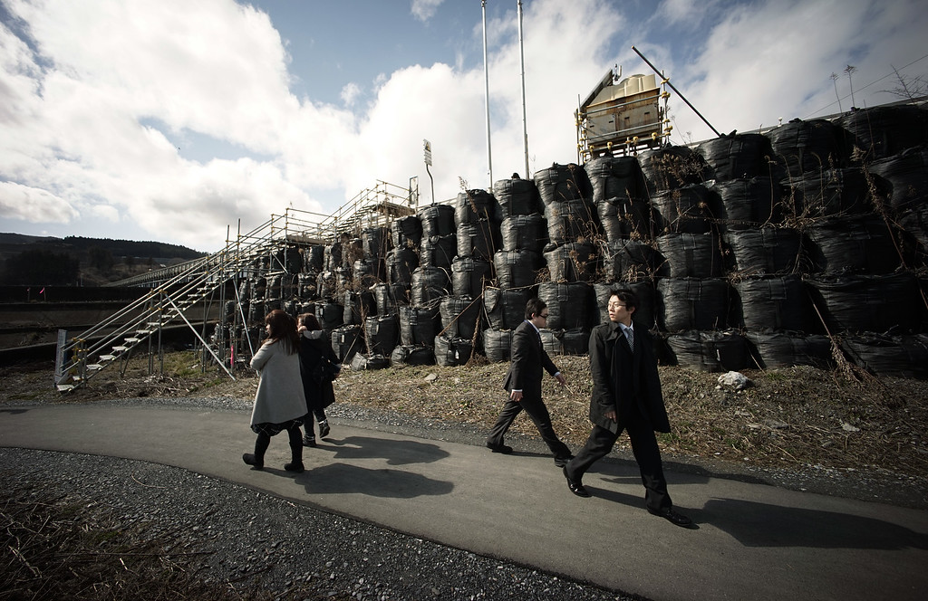 . In this Wednesday, March 4, 2015 photo, people walk next to a temporary breakwater in the Tsunami damaged area in Rikuzentakata, Iwate Prefecture, northeastern Japan. Still struggling to recover, the tsunami-hit region of northeastern Japan marks the fourth anniversary of the March 11, 2011, disaster Wednesday with simultaneous moments of silence along the coast. (AP Photo/Eugene Hoshiko)