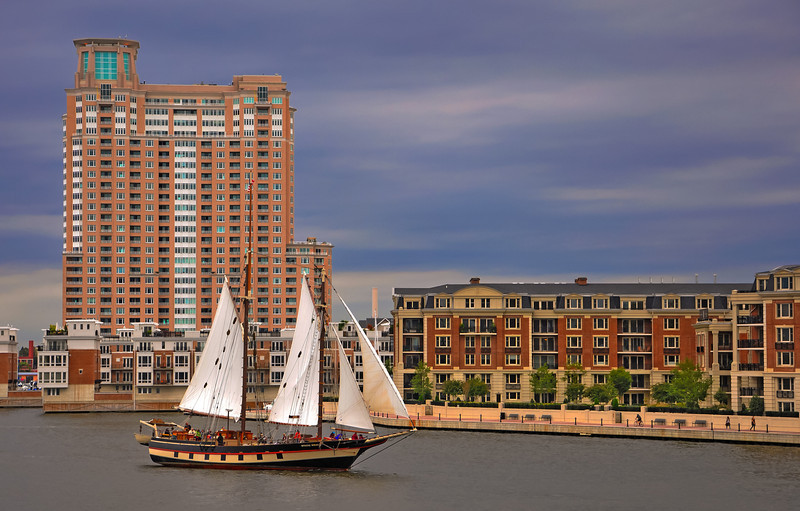 Apartment buildings and a sailboat seen in the Inner Harbor of Baltimore, Maryland.