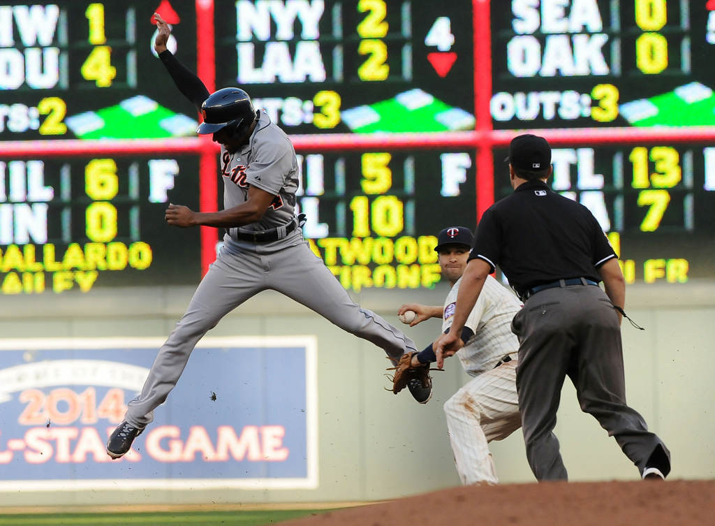 . The Tigers\' Austin Jackson jumps into the air after getting tagged by Twins second baseman Brian Dozier as Dozier turns to throw to first for a double play in the fifth inning.  (Pioneer Press: Sherri LaRose-Chiglo)