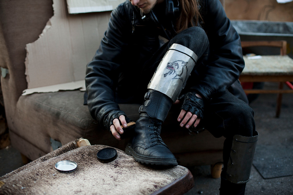 . A member of a self defense volunteer group, with makeshift shin guards bearing a picture of a wolf, polishes his boots in Kiev\'s Independence Square, Ukraine, Tuesday, March 11, 2014. (AP Photo/David Azia)
