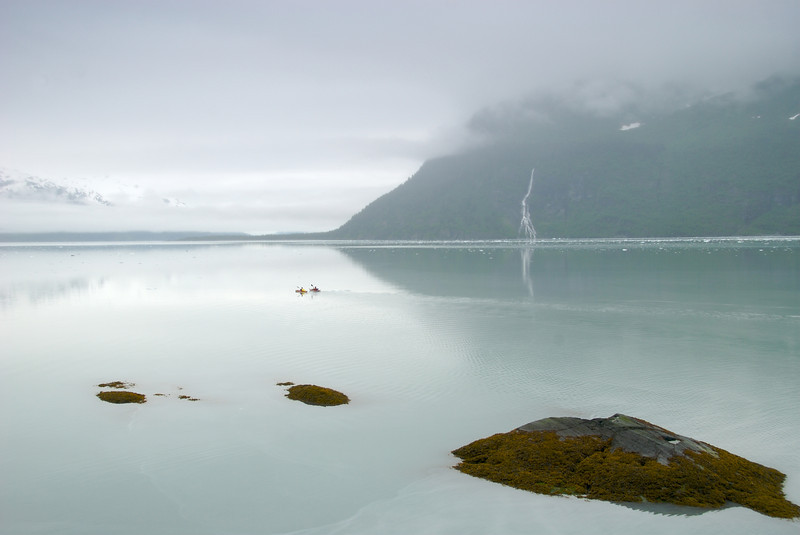 two sea kayakers paddle the Barry arm on a misty morning in the Prince William Sound, AK