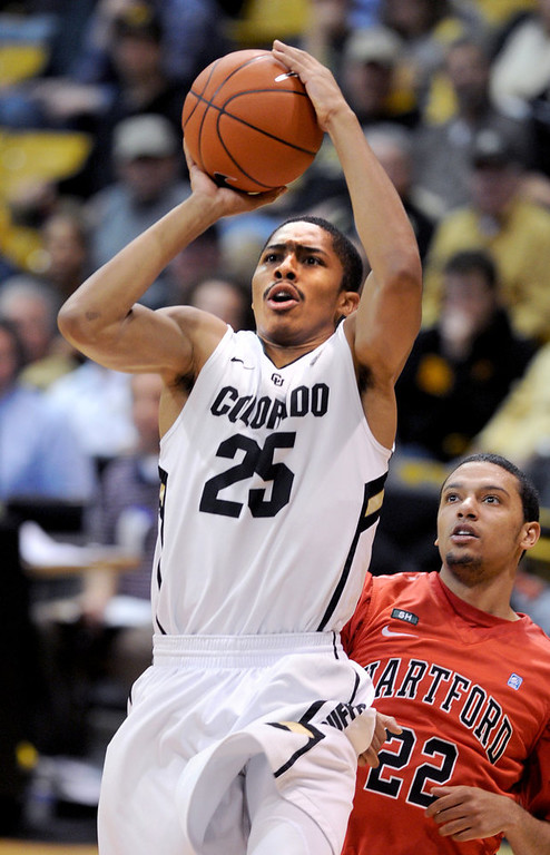 . Spencer Dinwiddie of CU gets past Evan Cooper (22) of Hartford on his way to the basket during the second half of the December 29, 2012 game in Boulder. (Cliff Grassmick / Daily Camera) December 29, 2012
