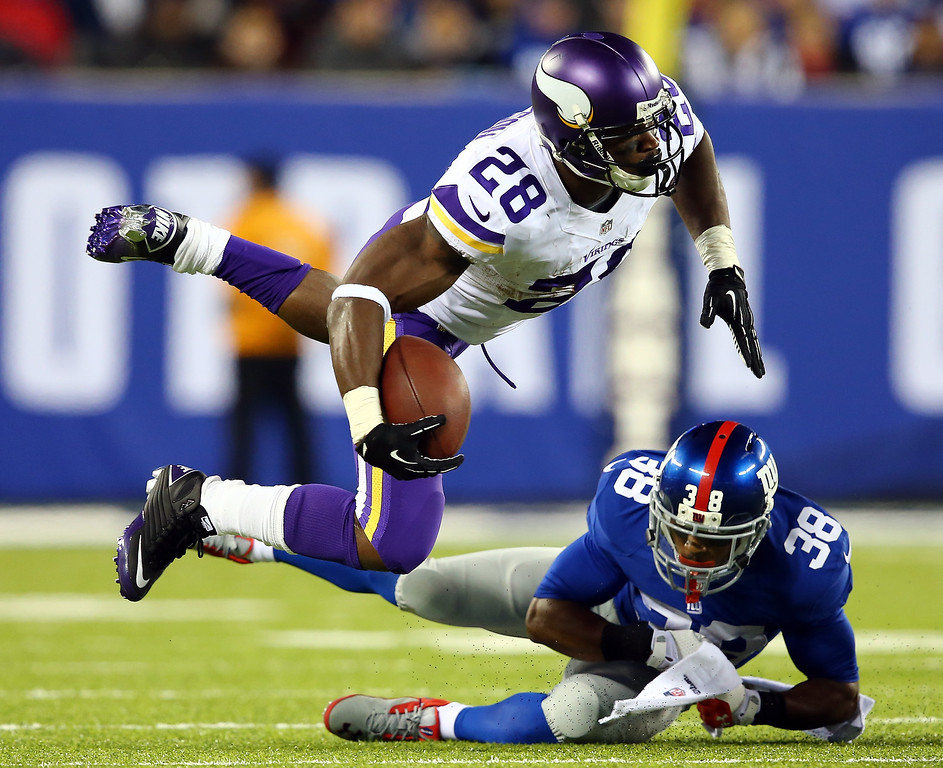 . Running back Adrian Peterson #28 of the Minnesota Vikings is tackled by cornerback Trumaine McBride #38 of the New York Giants during a game at MetLife Stadium on October 21, 2013 in East Rutherford, New Jersey.  (Photo by Elsa/Getty Images)