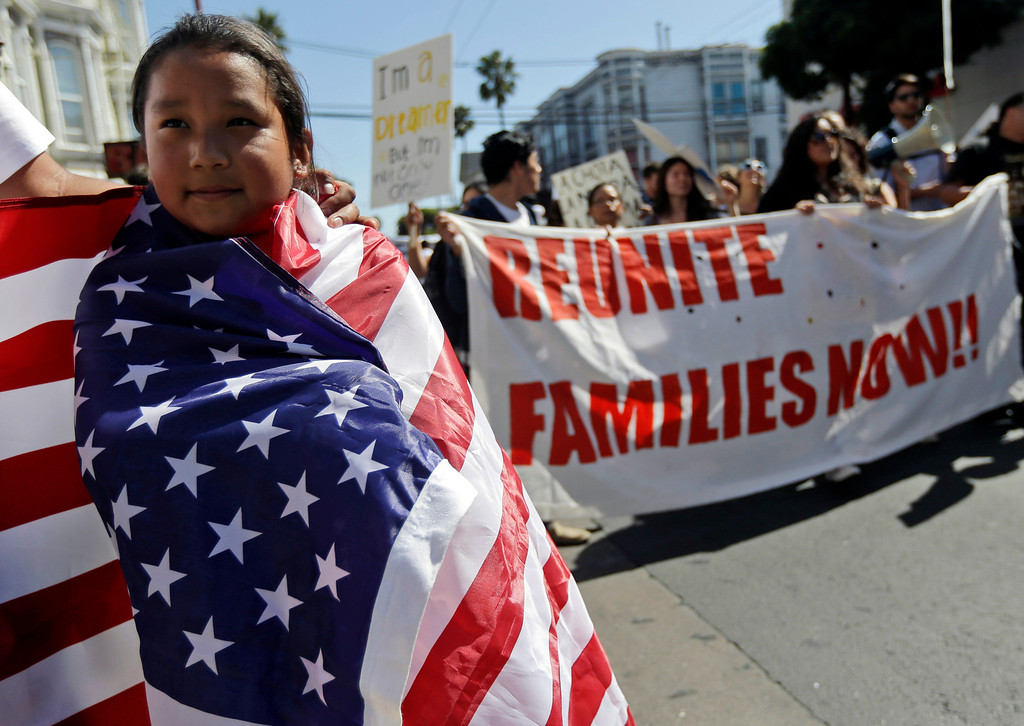 . Maria Fernanda Medina, 7, wraps herself in a United States flag as she marches with her father, Jorge, during a May Day demonstration in San Francisco, Wednesday, May 1, 2013.  Demonstrators demanded an overhaul of immigration laws Wednesday in an annual, nationwide ritual that carried a special sense of urgency as Congress considers sweeping legislation that would bring many of the estimated 11 million people living in the U.S. illegally out of the shadows. (AP Photo/Marcio Jose Sanchez)