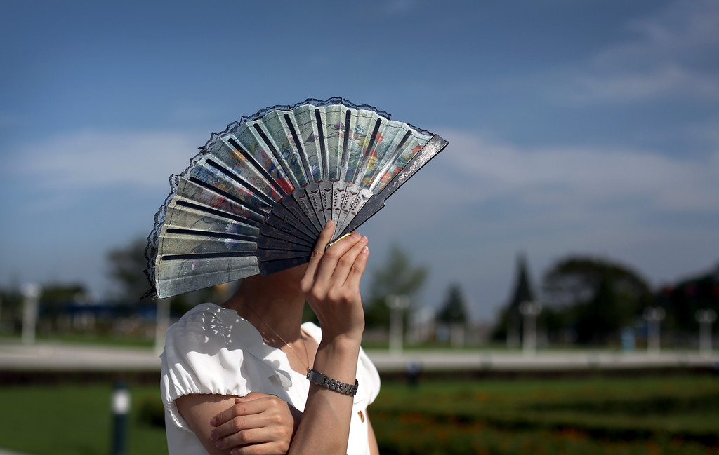 . A guide shields her face from the sun while touring the park surrounding Kumsusan Palce of the Sun, the mausoleum where bodies of the late leaders Kim Il Sung and Kim Jong Il lie embalmed on Thursday, July 25, 2013 in Pyongyang, North Korea. (AP Photo/Wong Maye-E)