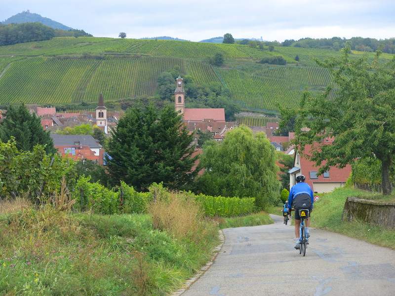 Anjum biking into a village in Alsace.