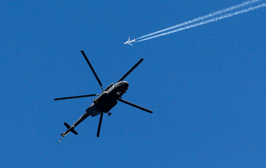. A military helicopter hovers over the mountain cluster as a passenger jet passes by prior to the 2014 Winter Olympics, Tuesday, Feb. 4, 2014, in Krasnaya Polyana, Russia. With militant groups threatening to attack during the next few weeks, security and the safety of competitors and visitors to the coastal area and in the nearby mountains that will host the events has become both heightened and inescapable. (AP Photo/Dmitry Lovetsky)