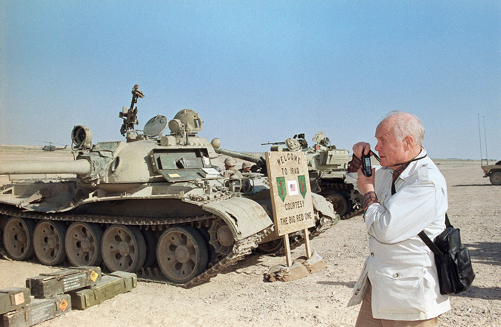 ". U.S. Sen. John Glenn (D-Ohio), pauses to take a snapshot of one of a group of destroyed Iraqi T-72 tanks on display at the captured Iraqi air base at Safwan, March 16, 1991. Glenn was among a group of U.S. senators who paid a visit to the U.S. 1st Infantry Division at the air base. In front of the tank is a sign which reads: ""Welcome to Iraq courtesy of the Big Red One.\"" (AP Photo/Roberto Borea)"