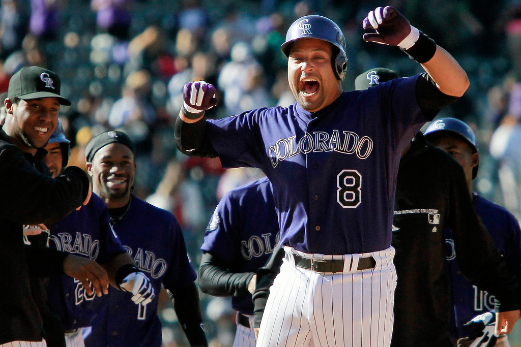 . Colorado Rockies\' Yorvit Torrealba (8) celebrates his 12th-inning, RBI single that scored Wilin Rosario to defeat the Atlanta Braves 6-5 in a baseball game, Wednesday, April 24, 2013, in Denver. (AP Photo/Barry Gutierrez)