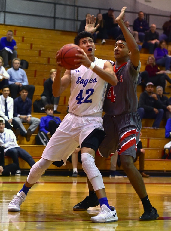. Broomfield High School\'s Devin Martinez looks to the basket against Denver East\'s Ja\'Shawn Chisel during their game in the Fairview Festival on Wednesday. For More photos go to bocopreps.com Paul Aiken Staff Photographer Dec 6 2017