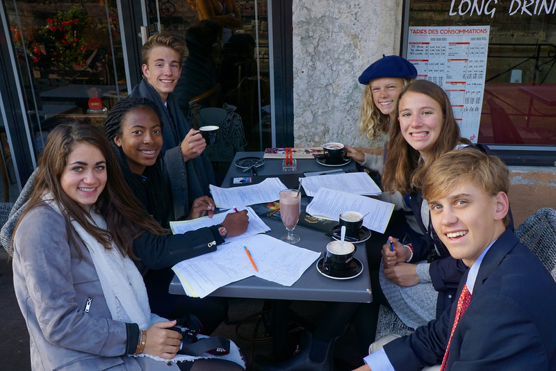 Lily, Ashley, Dylan, Elsie, Emily, and Billy organizing outside a cafe