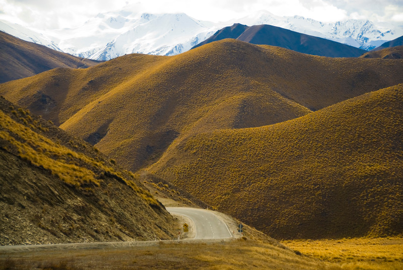 The road winds through the tussock lands of Lindis Pass in Central Otago, New Zealand