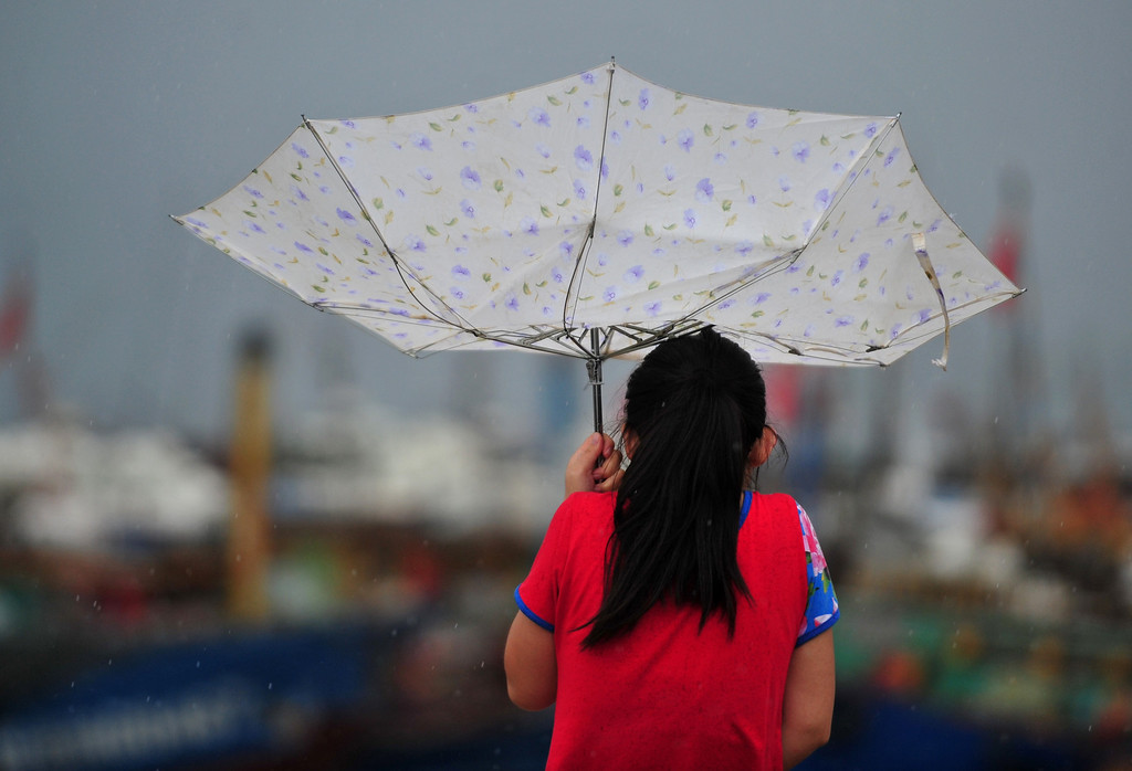 . In this photo provided by China\'s Xinhua News Agency, a woman struggles with an umbrella in the strong wind at a harbor in the Luoyuan County, southeast China\'s Fujian Province, Saturday, July 13, 2013. A powerful typhoon surged across northern Taiwan on Saturday, killing at least one person before moving to southeast China and forcing the evacuation of hundreds of thousands of people from a coastal province. (AP Photo/Xinhua, Wei Peiquan)