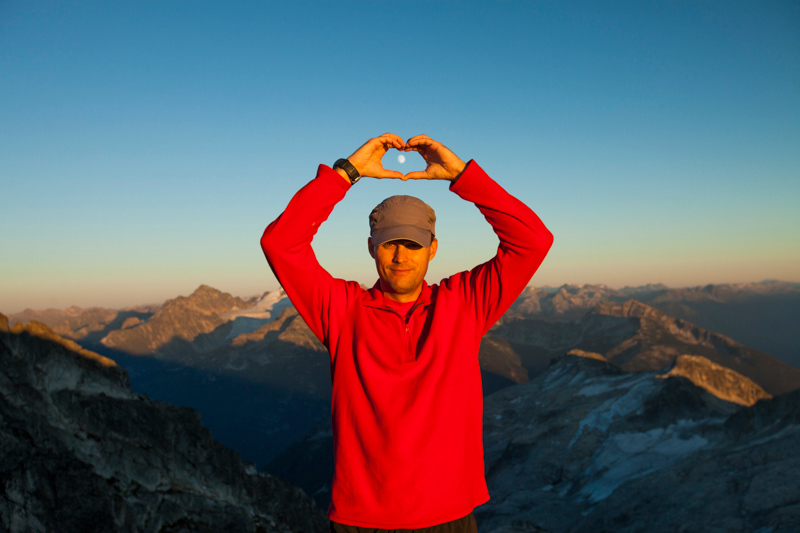 A hiker raises his hands to circle the full moon.