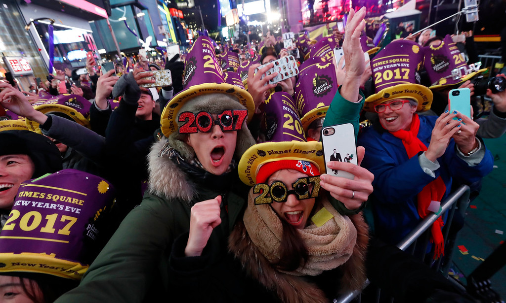 . Mikito Horino, left, and his wife, Taki Horino, from Japan, count the final seconds before the new year during the New Year\'s Eve celebration at Times Square, Saturday, Dec. 31, 2016, in New York. (AP Photo/Julio Cortez)