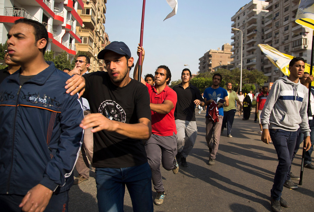 . Supporters of Egypt\'s ousted President Mohammed Morsi run after army soldiers fire into the air during a protest in Cairo, Egypt, Friday, Oct. 11, 2013. Thousands of Morsi supporters took to the streets Friday in several cities, commemorating 100 days since Egypt\'s first democratically elected president was ousted by the military following mass protests calling for his resignation. (AP Photo/Hassan Ammar)