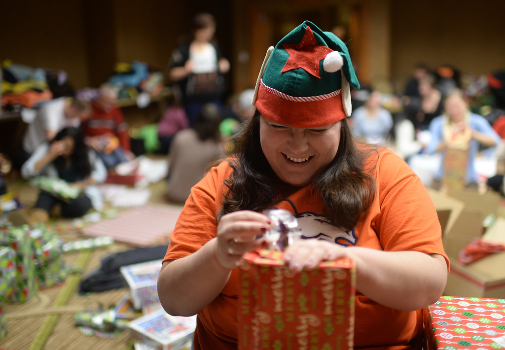 ". DENVER, CO. DECEMBER 21: Leanna Tolmich of Denver is wrapping Christmas gift during the annual Father Woody Christmas Party in Denver, Colorado December 21, 2013. In advance of handing out 5,000 gifts, volunteers are doing a ""wrapping party\"" at the Sheraton Denver Downtown Hotel. (Photo by Hyoung Chang/The Denver Post)"