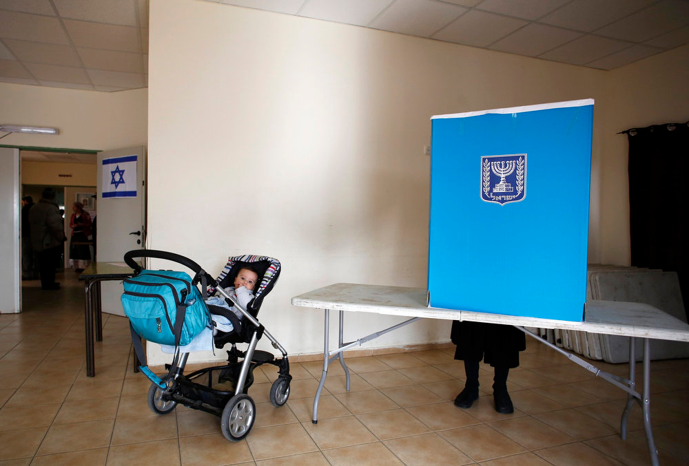 . A baby waits in a pram as her mother casts her ballot for parliamentary elections at a polling station in the West Bank Jewish settlement of Elon Moreh, near Nablus January 22, 2013. Israelis look set to elect Prime Minister Benjamin Netanyahu to a third term with a smaller majority on Tuesday, pushing the Jewish State even further to the right, away from peace with Palestinians and towards a showdown with Iran. REUTERS/Baz Ratner