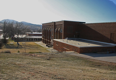 "Higbee recalled the spectacular views enjoyed by students at the old high school location.  This contemporary view shows Crow Peak in the background.  Classroom students on the south side of the building would have a splendid view of Spearfish Mountain.  From a rather humble wresting team in 1956-57, when the program was started, Spearfish went on to win the state championship in 1960 and was recognized as a wrestling powerhouse throughout the 1960s.   Signs were erected along the roads coming into town proclaiming Spearfish as ""State Wrestling Capitol of South Dakota.""  When the old high school closed in 1979, there were 107 students in the graduating class."
