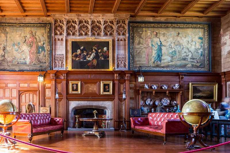 red leather sofas flank a fireplace in Alnwick Castle