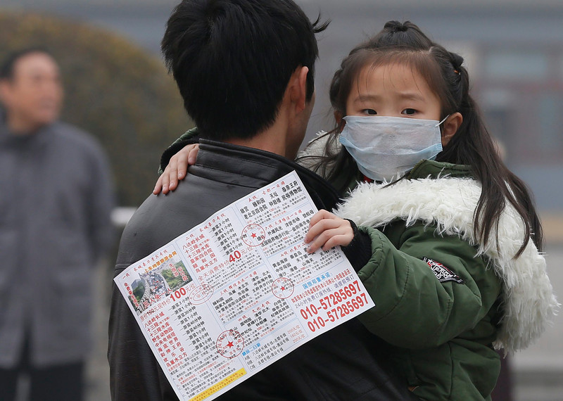 . A child wears a protective mask while carried by her father at the Tiananmen Square amidst smog in Beijing, China, 26 February 2014. Chinese authorities ordered new measures to curb choking air pollution this week, amid growing public alarm at the density of harmful micro-particles hovering over about 15 per cent of the country. The PM 2.5 air quality index measuring fine particle air pollution in Beijing has reached over 500, or \'hazardous\' levels on 26 February.  (EPA/ROLEX DELA PENA)