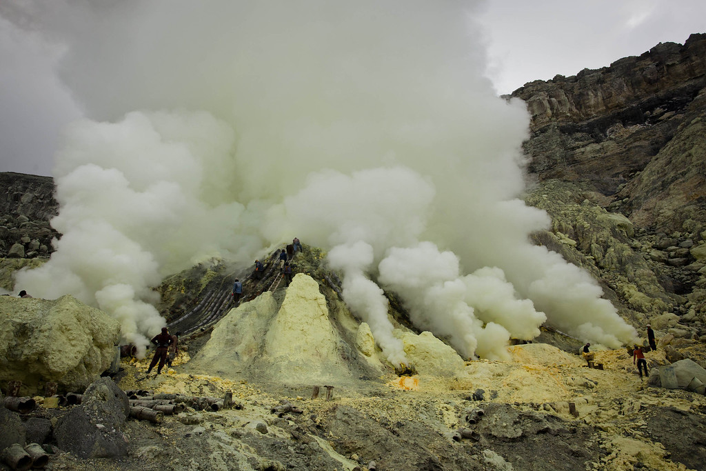 . Miners extracts sulphur from pipe at the flow crater during an annual offering ceremony on the Ijen volcano on December 17, 2013 in Yogyakarta, Indonesia. (Photo by Ulet Ifansasti/Getty Images)
