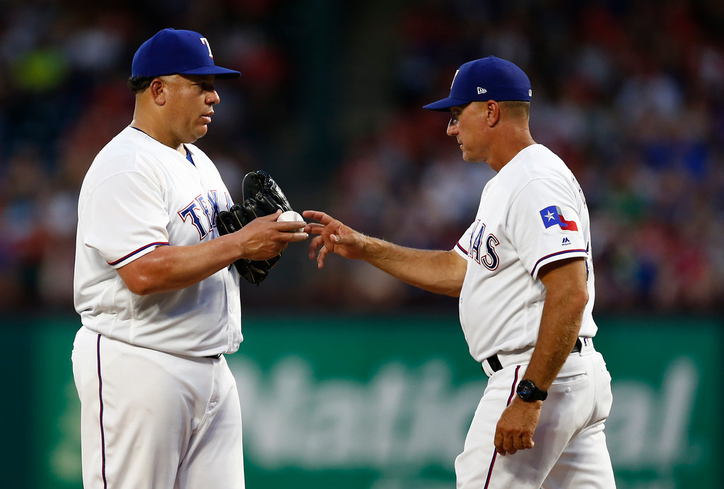. Texas Rangers starting pitcher Bartolo Colon, left, hands the ball over to manager Jeff Banister during the fifth inning of the team\'s baseball game against the Cleveland Indians, Saturday, July 21, 2018, in Arlington, Texas. (AP Photo/Jim Cowsert)