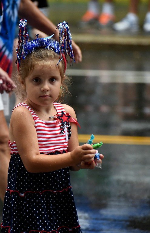 . Kayla Rice/Reformer A girl prepares to throw a large handful of candy while walking in the Brattleboro Fourth of July parade on Friday.