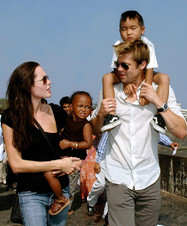 """. MUMBAI, INDIA:  US actors Angelina Jolie (L), daughter Zahara (2L), husband Brad Pitt (R), and son Maddox take a stroll on the seafront promenade in Mumbai, 12 November 2006.  Jolie and Pitt are in Mumbai, India\'s financial hub, to shoot for her film \""""A Mighty Heart\"""", based on the life of the slain Wall Street Journal reporter Daniel Pearl in which Jolie portrays Marianne, the wife of Daniel Pearl.  (STR/AFP/Getty Images)"""