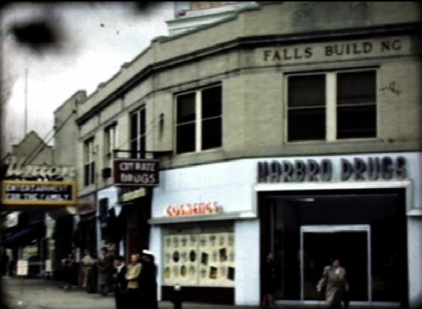 """The Falls Building - Harbro Drugs and The Union Movie Theater shown. A sign indicates that they offer the some fine """"Cut Rate Drugs""""."""
