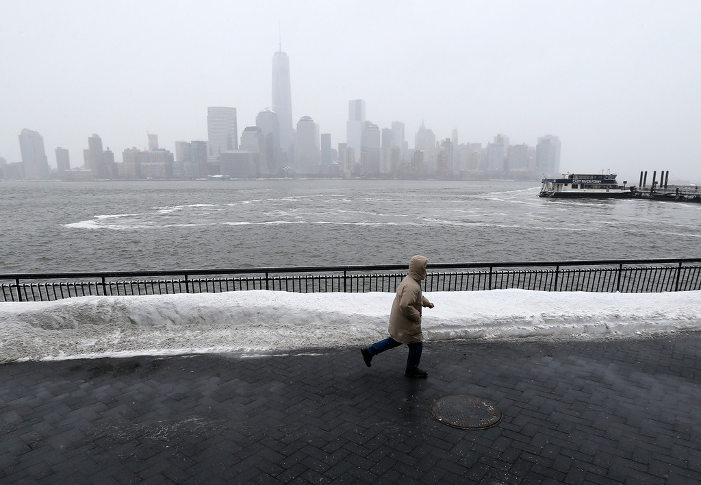 . A person runs to catch the New York Waterway ferry on a walkway that was plowed following an overnight snowstorm, Tuesday, Jan. 27, 2015, in Jersey City, N.J.  A storm packing blizzard conditions spun up the East Coast early Tuesday, pounding coastal eastern Long Island into Maine with high winds and heavy snow. (AP Photo/Julio Cortez)