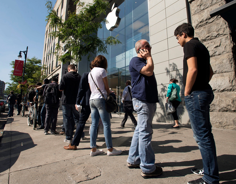 . Customers  wait in line for the latest versions of the iPhone that went on sale Friday, Sept.  20, 2013 in Montreal. Friday is the first time Apple is releasing two different iPhone models at once. (AP Photo/The Canadian Press, Ryan Remiorz)