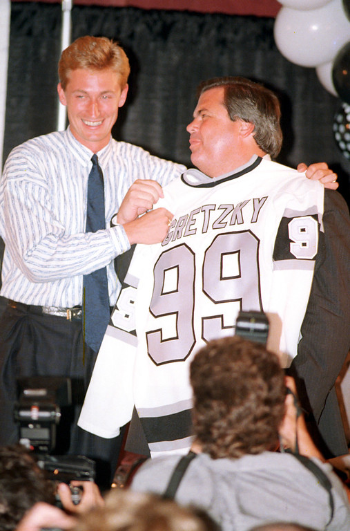 . Canadian hockey player Wayne Gretzky, left, smiles as he holds his new Los Angeles Kings jersey against Kings owner Bruce McNall at a news conference in Los Angeles, Ca., late Tuesday night, Aug. 10, 1988.  Gretzky was traded from the Edmonton Oilers in one of the biggest sports deals in history.  (AP Photo/Reed Saxon)