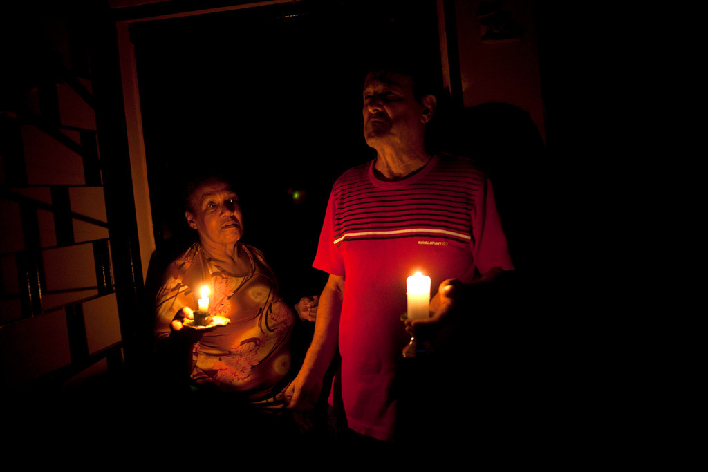 ". In this April 8, 2013 photo, Pedro Martinez, 73, right, and his wife Aura, 60, hold lit candles during a power outage at their home in Valencia, Venezuela. ""This happens nearly every day,\"" Martinez says of the blackout. It\'s was the day\'s second outage. The first struck just after noon. Outside Venezuela\'s capital, power outages, food shortages and unfinished projects abound; important factors heading into Sunday\'s election to replace Venezuela\'s late President Hugo Chavez, who died last month after a long battle with cancer. Polls show that support for acting President Nicolas Maduro, Chavez\'s hand-picked successor, may be eroding and constant power outages are a testament to the neglect many Venezuelans consider inexcusable in this major oil-producing state. (AP Photo/Ramon Espinosa)"