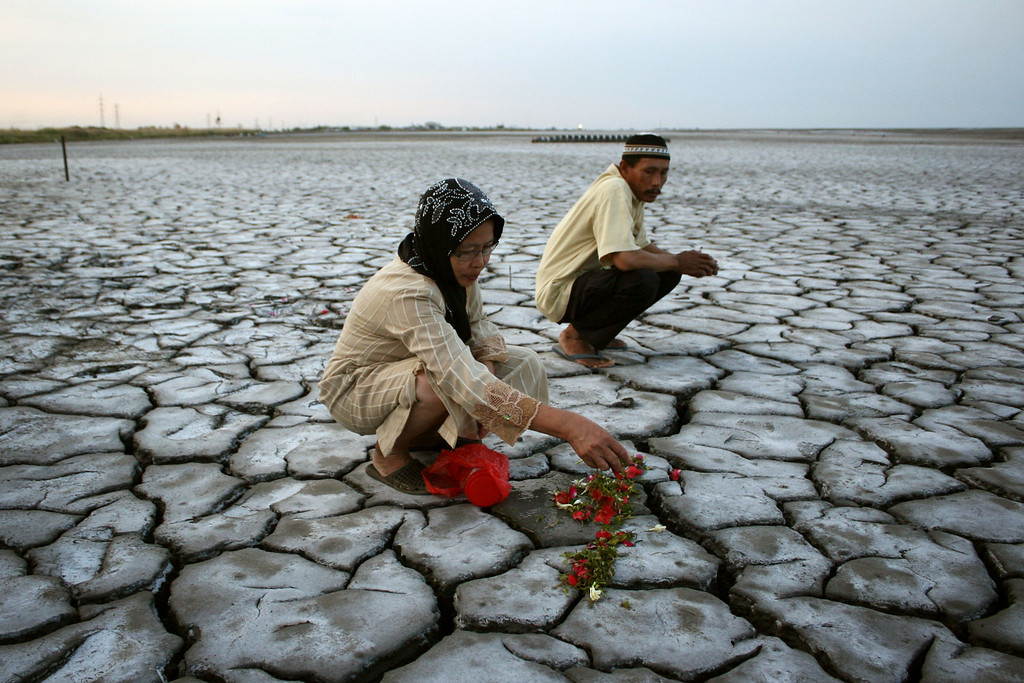 . In this photograph taken on August 7, 2013, an Indonesian woman offers flowers on dried volcanic mud for family members who died during a volcano eruption in Sidoarjo in eastern Java island, as Indonesians mark Eid al-Fitr with pilgrimages to cemeteries to remember their dead. The May 2006 disaster killed 12 people, displaced nearly 50,000 and buried 13 villages. M. ANDIKA/AFP/Getty Images