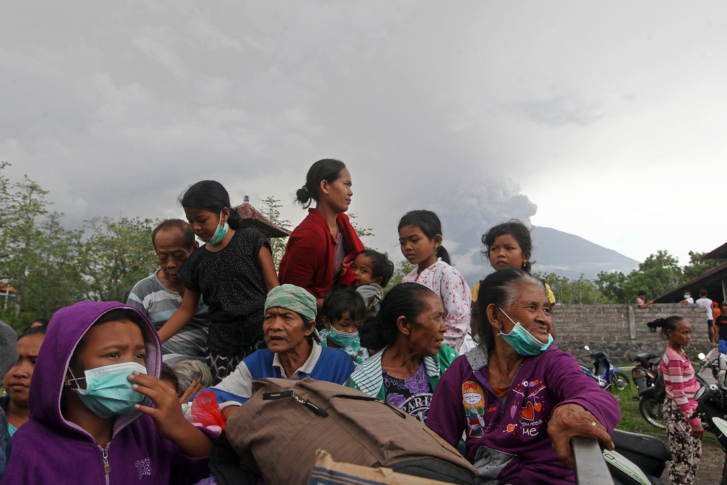 . Villagers sit on a truck during an evacuation following the eruption of Mount Agung, seen in the background, in Karangasem, Indonesia, Sunday, Nov. 26, 2017. The volcano on the Indonesian island of Bali has rumbled into life with a series of eruptions that temporarily disrupted some international flights to the popular tourist destination and dusted nearby resorts and villages with a thin layer of ash. (AP Photo/Firdia Lisnawati)