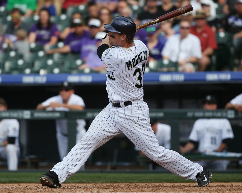 . Colorado Rockies\' Justin Morneau follows the flight of his two-run home run against the Philadelphia Phillies in the seventh inning of the Phillies\' 10-9 victory in a baseball game in Denver on Sunday, April 20, 2014. (AP Photo/David Zalubowski)