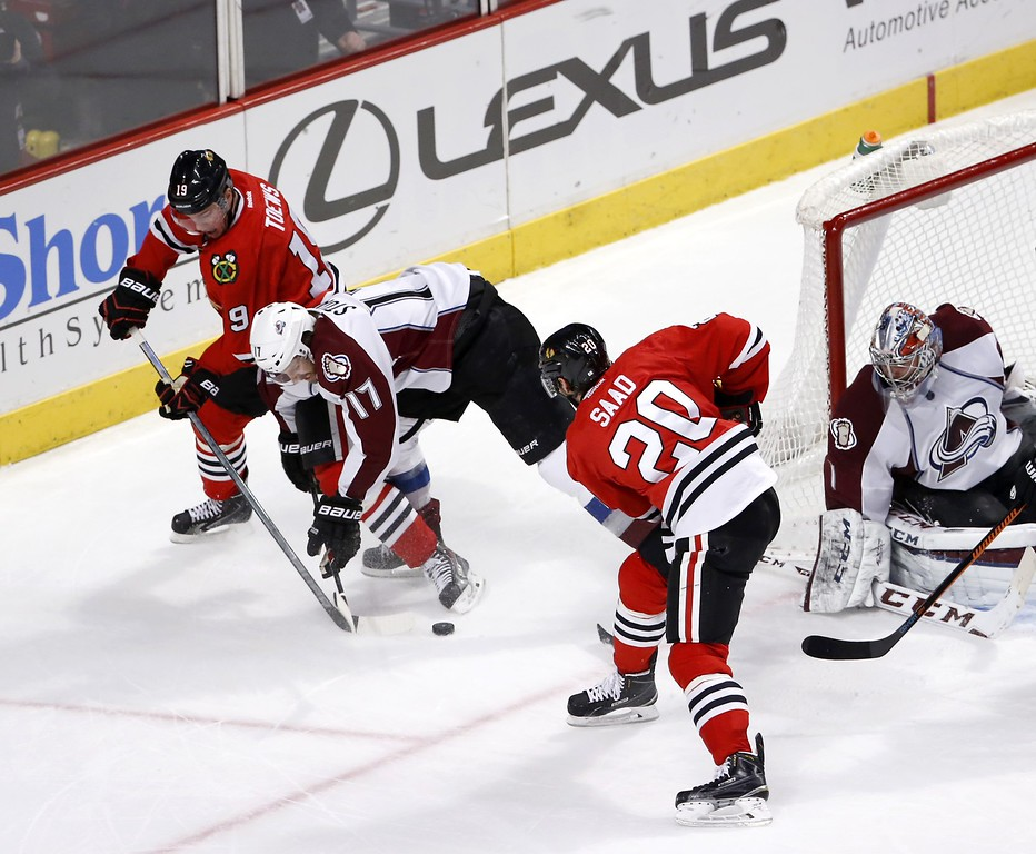 . Colorado Avalanche defenseman Brad Stuart (17) keeps Chicago Blackhawks center Jonathan Toews (19) and Brandon Saad (20) away from the puck as goalie Semyon Varlamov watches, during the third period of an NHL hockey game Tuesday, Jan. 6, 2015, in Chicago. The Avalanche won 2-0. (AP Photo/Charles Rex Arbogast)