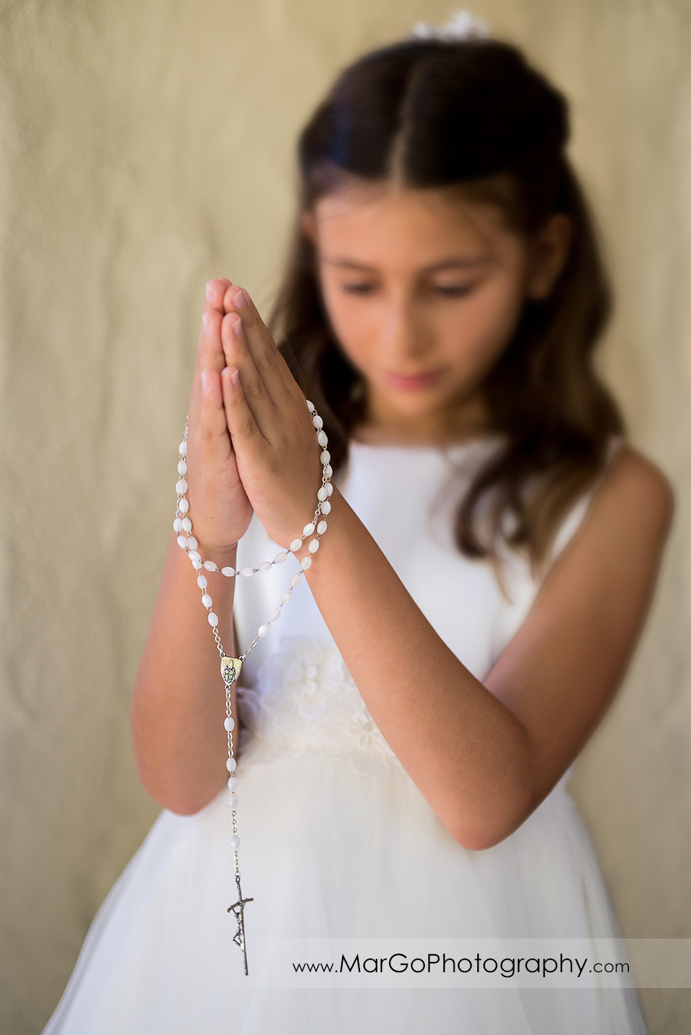 first communion girl in white dress with rosary in folded hands at Cafe Wisteria in Menlo Park
